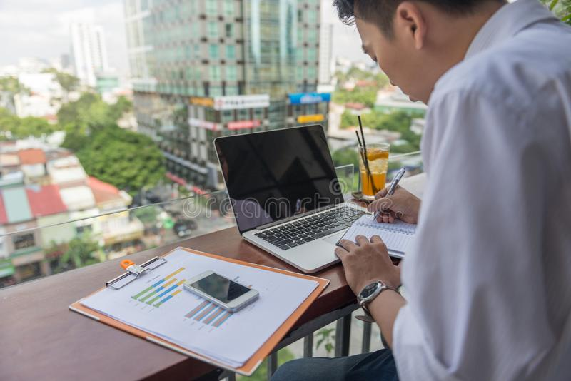 Hard-working guy writing on notebook. Young hard-working guy concentrate on writing on notebook stock images