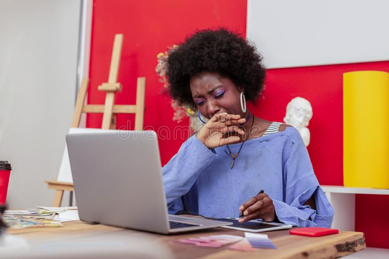Hard-working interior designer yawning while feeling sleepy. Feeling sleepy. Hard-working interior designer yawning while feeling sleepy after working for too royalty free stock photo