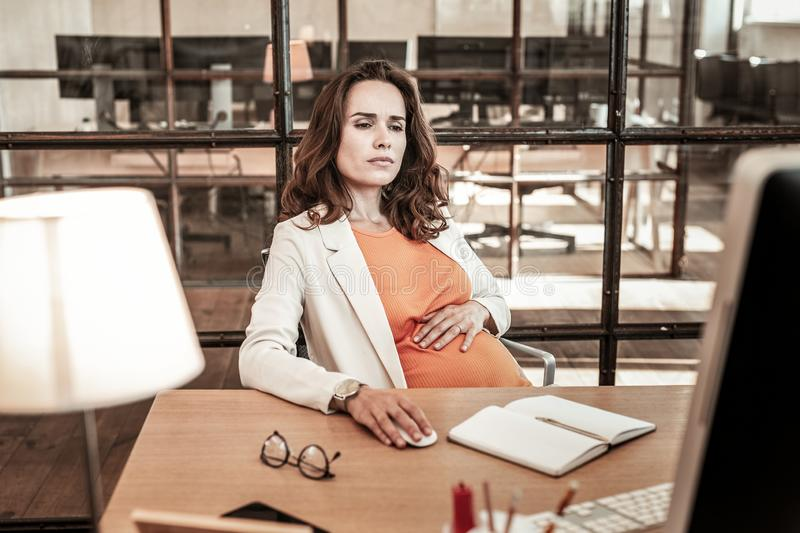Concentrated dark-haired woman sitting in office armchair and working. Hard-working lady. Concentrated dark-haired woman sitting in office armchair and working stock photo