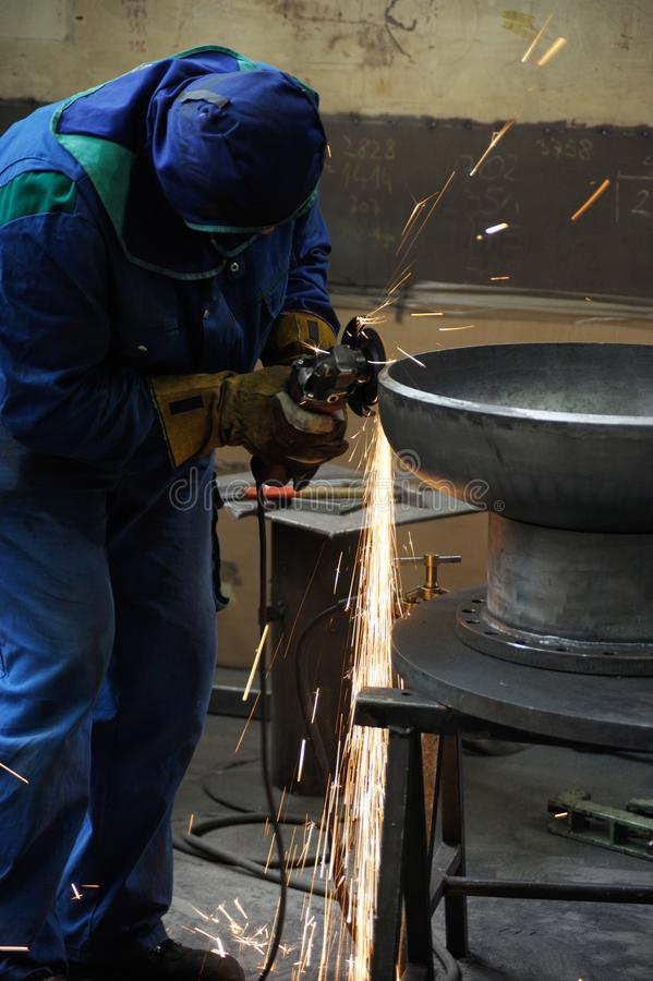 Hard working man at the metal industry. Hard working man with metal shaping tool in action wearing mask and gloves, vertical composition royalty free stock image