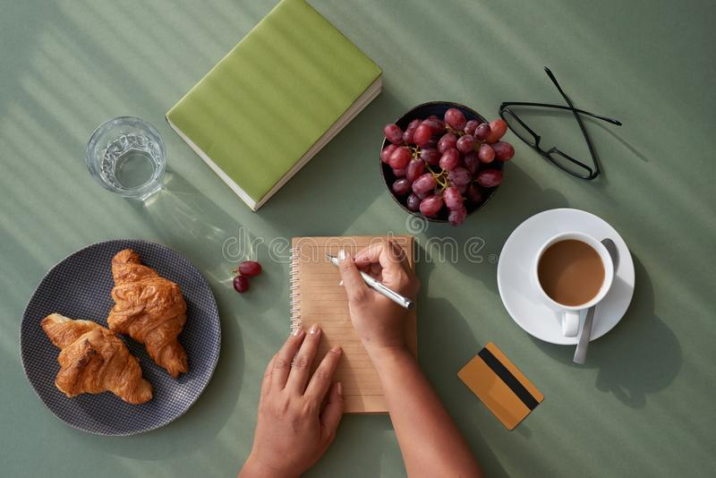 Hard-Working Manager Having Breakfast. Directly above view of hard-working manager taking necessary notes while sitting at kitchen table at breakfast, appetizing royalty free stock photography