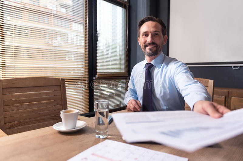 Hard working responsible manager giving you the documents. Work reports. Nice cheerful responsible manager sitting at the table and putting out his hand while stock photography