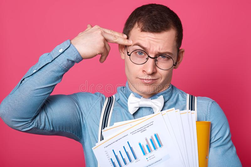Hard working stressed athletic student touches his temple with two fingers, wants to kill himself, tired of working hard, having. Lot of paperwork, posing stock photography