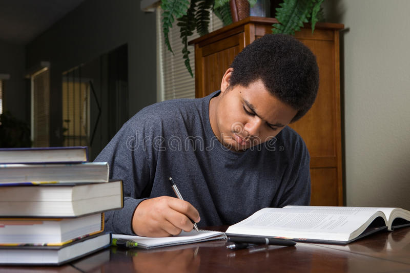 Hard working young black student. Hard working African American teenaged student, studying at home with stack of books and study materials stock images