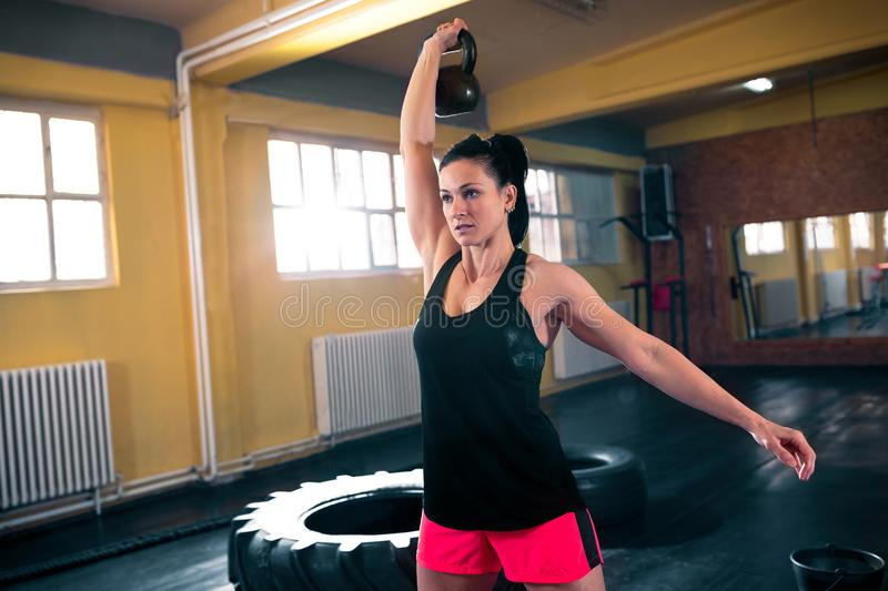Hard workout with kettlebell, woman doing intense train. Hard workout with kettlebell, young woman doing hard intense training stock image