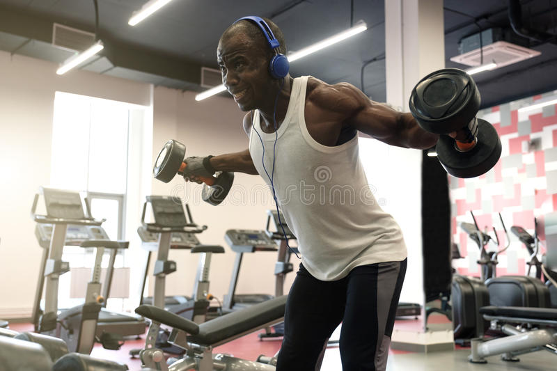 Hard workout. Muscular black man doing exercises with dumbbells at gym royalty free stock photography