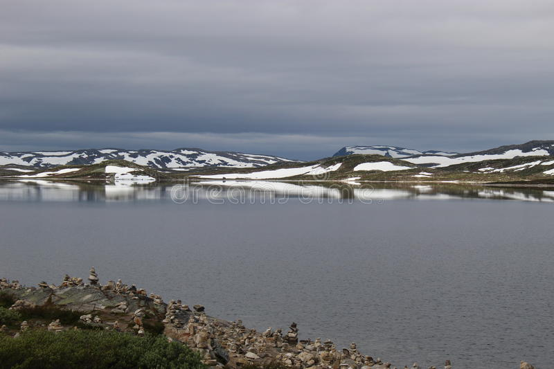 The Hardangervidda Plateau in Hallingskarvet National Park, Norway, Europe, with lake Ustevatn. In August, there is still snow on the mountains royalty free stock image