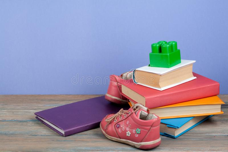 Hardback colorful books, toy, shoes on wooden table. Back to school. Copy space for text. Education business concept. stock photography
