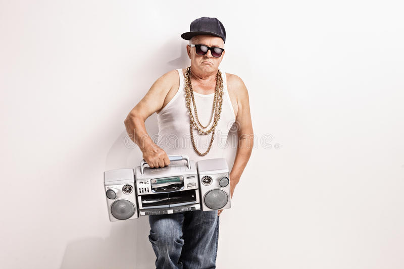 Hardcore senior rapper holding a ghetto blaster. And looking at the camera stock photography