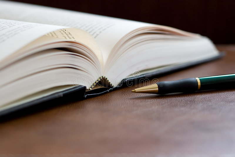 Hardcover Book and Pen. A hardcover book lays open on a brown leather desk with pen royalty free stock photos
