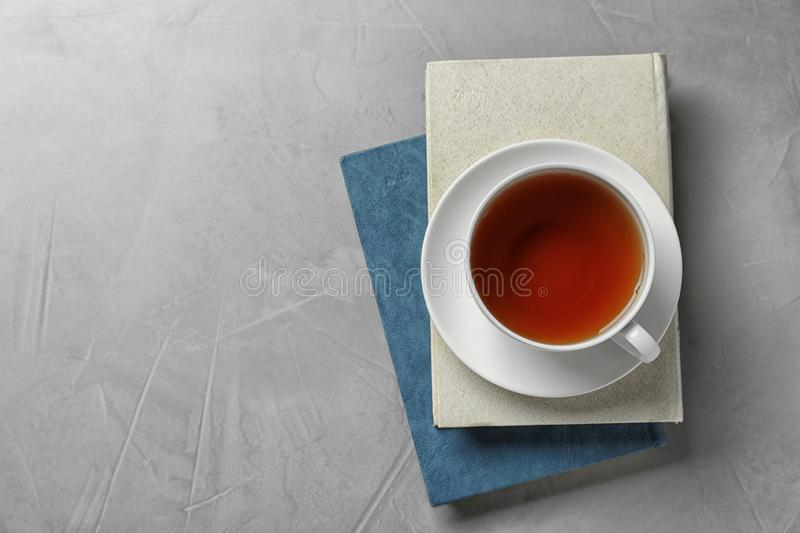 Hardcover books and cup of tea on stone background, top view. Space for text. Hardcover books and cup of tea on grey stone background, top view. Space for text stock photos