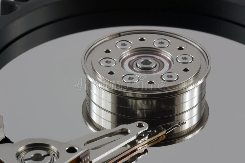 Harddisk - extreme close-up. Extreme Close-Up of rotor and read/write head of SCSI hard drive with reflections royalty free stock photos