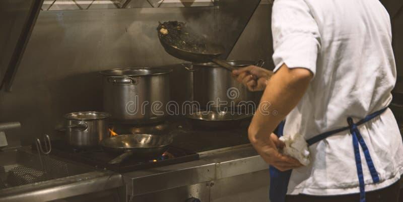 Harde arbeiders internationale chef-kok die heerlijke platen in een internationaal restaurant koken stock foto's