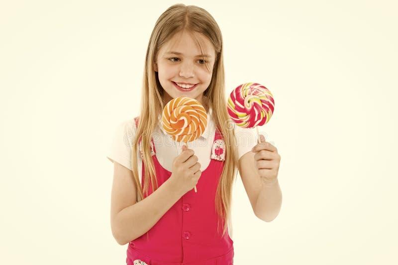 Harde keus De vrolijke lollys van de meisjeholding in haar handen en het glimlachen terwijl status op wit Het meisje kan stock foto's