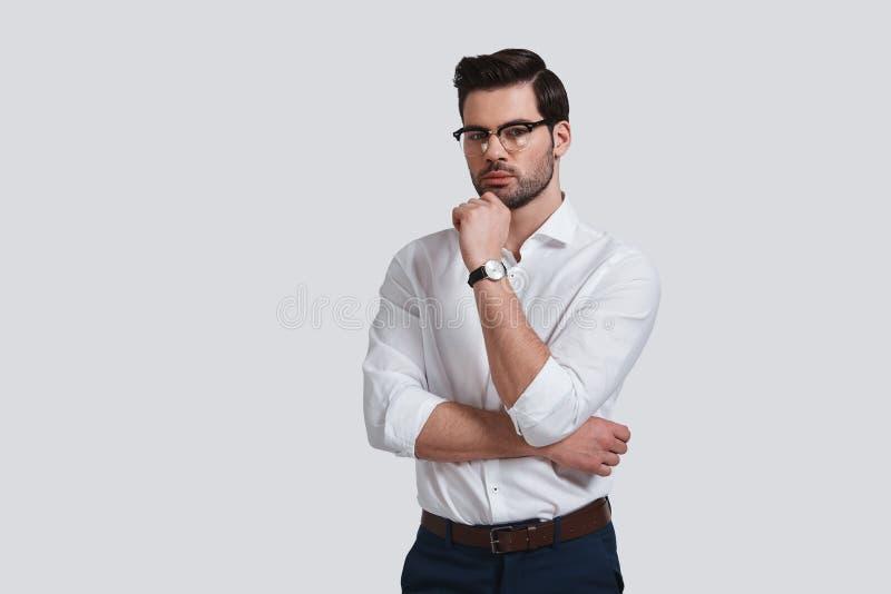 Harde keus Knappe jonge mens in formalwear houdende hand o stock afbeelding