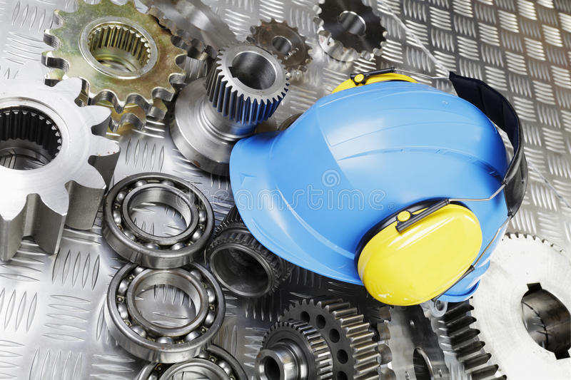 Hardhat and engineering. Workers hardhat, earmuffs, engineering and machine parts, gears and bearings, conceptual image stock photography
