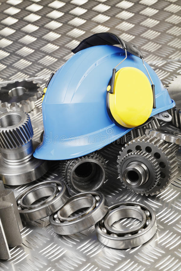 Hardhat and engineering. Workers hardhat, earmuffs, engineering and machine parts, gears and bearings, conceptual image royalty free stock images