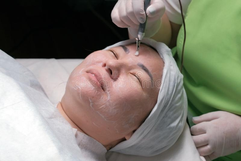 Hardware cosmetology. Relaxed Muslim woman with eyes closed during a therapeutic disincrustation procedure. Asian girl on galvanic royalty free stock image