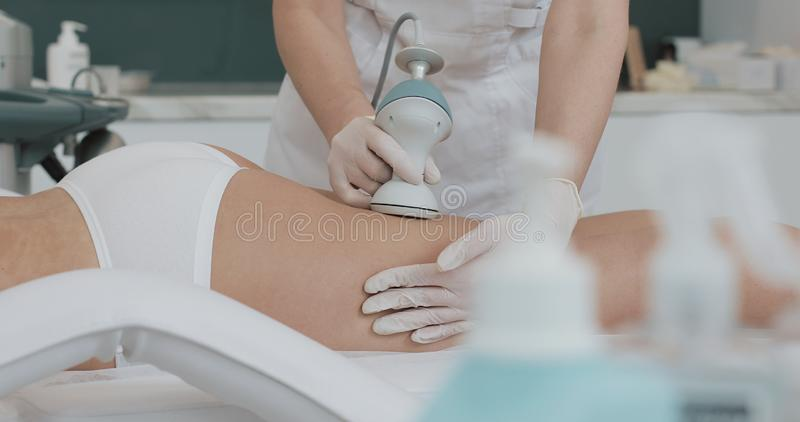 Hardware figure correction. Machine cosmetology. Beautiful woman having cavitation, procedure removing cellulite on her royalty free stock photography
