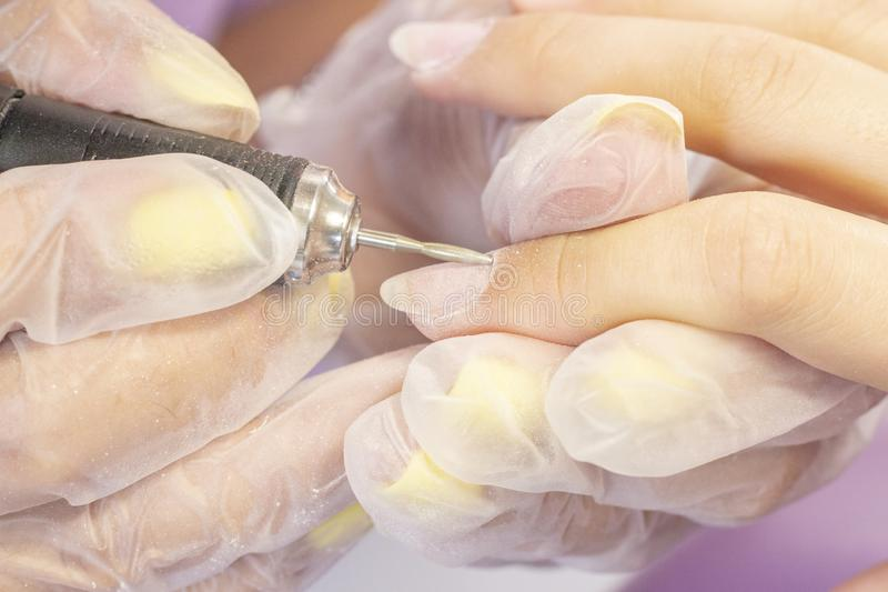 Hardware manicure. manicurist uses a manicure machine to process nail plate and nail file royalty free stock photo