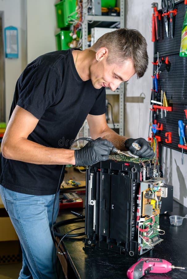 Hardware repairman repairing broken printer fax machine royalty free stock photos