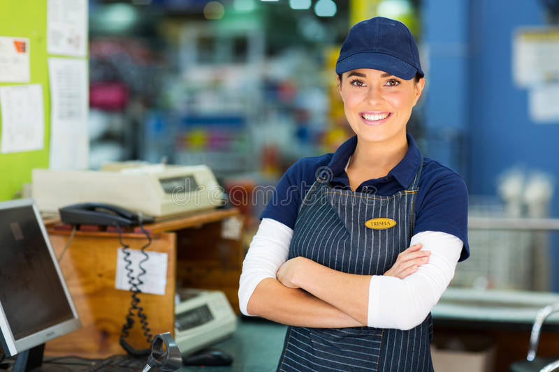 Hardware store cashier. Happy female hardware store cashier with arms folded stock photography