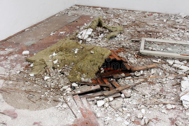 Wooden floor destroyed by water and covered with rubble stock photography