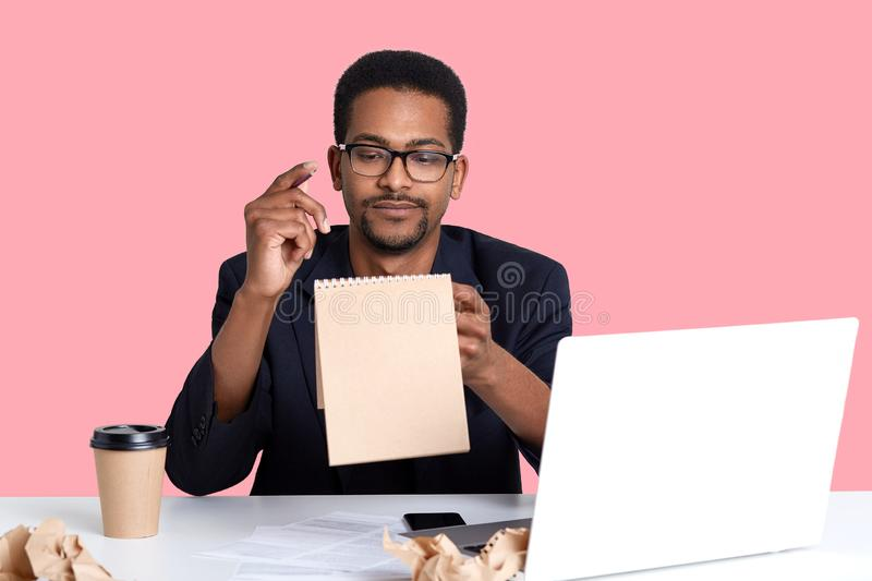 Hardworking dark skinned student sits at desktop, holds pen in hands, tries to write report, makes notes in his notebook. Handsome stock images