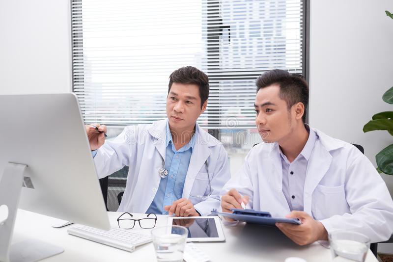 Hardworking doctors reviewing patient`s file stock image