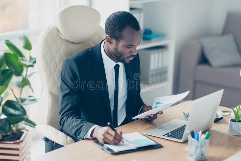 Hardworking financier sitting at desktop in workstation, workplace, watching, looking at documents, report, making notes in his n. Otebook royalty free stock image