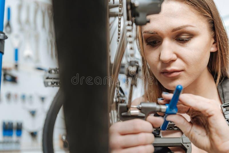 Hardworking jonge technicus die het pedaal van de fiets bevestigen stock foto's