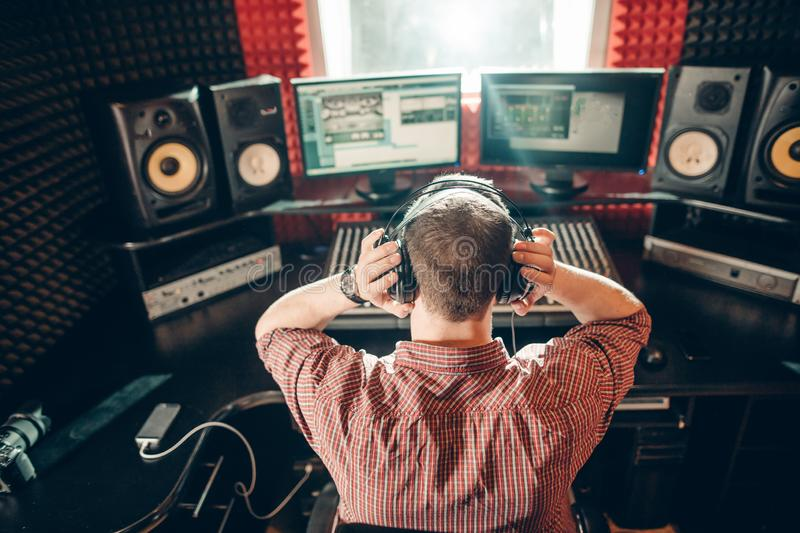 Hardworking man is concentrated on cutting the song. Back view photo. music industry royalty free stock photography
