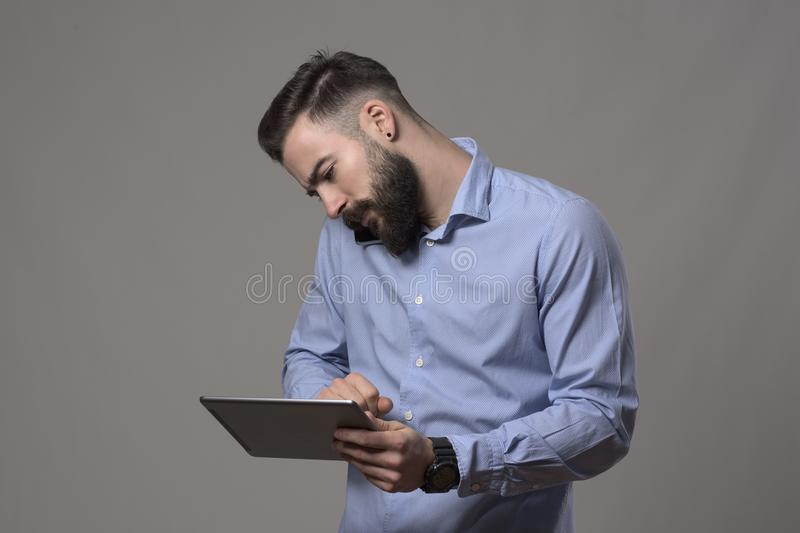 Hardworking multitasking busy business man cradling mobile phone on shoulder talking and using tablet computer. On gray studio background stock photos