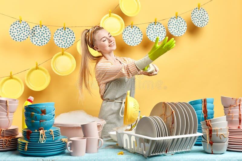 Hardworking positieve huisvrouw die op handschoenen zetten stock fotografie
