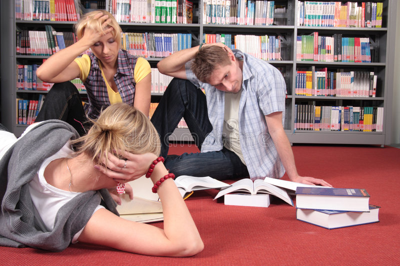 Hardworking students in the library stock photography