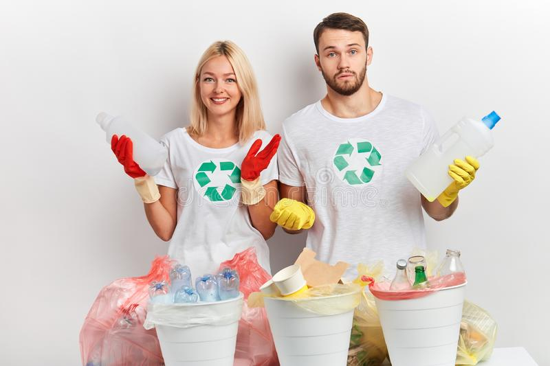 Hardworking young man and woman being surprised with much litter. Hardworking young men and women with recycling symbols on their white T-shirts being surprised stock images