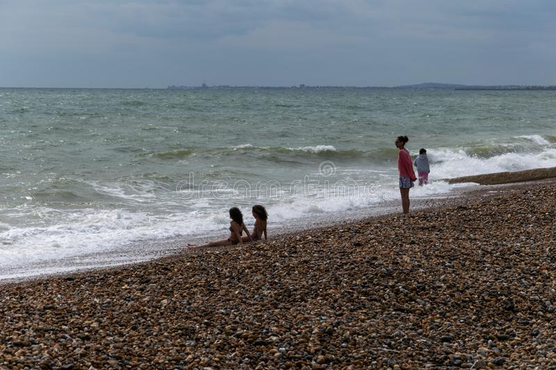 Hardy bathers on the beach. On a grey summer`s day in Brighton, Sussex royalty free stock photography