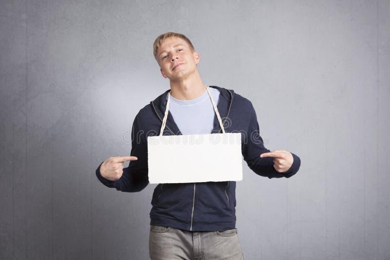 Hardy mężczyzna wskazuje palce przy pustym signboard. zdjęcia royalty free