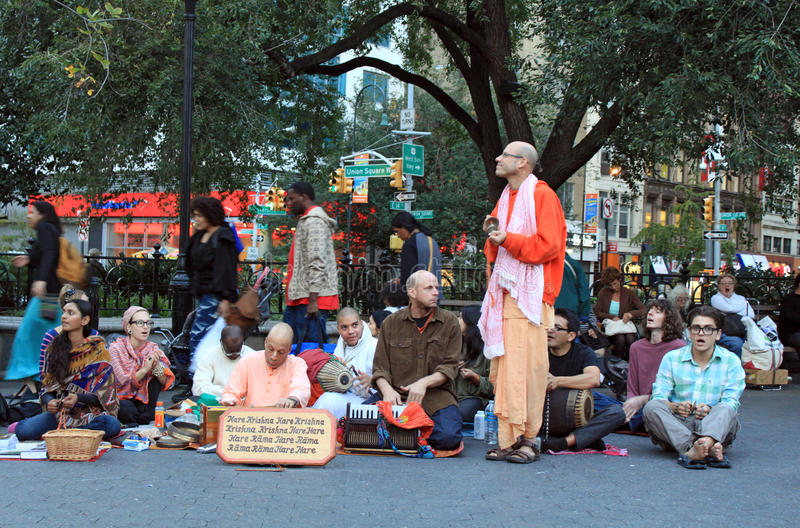 Hare Krishna sit and sing. Members of Hare Krishna sit and sing in street of New York City stock image