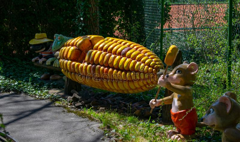 Hare steals corn kernels from the corncob in the amusement park Märchenwald, Wolfratshausen, Bavaria-April 18,2018 stock photos