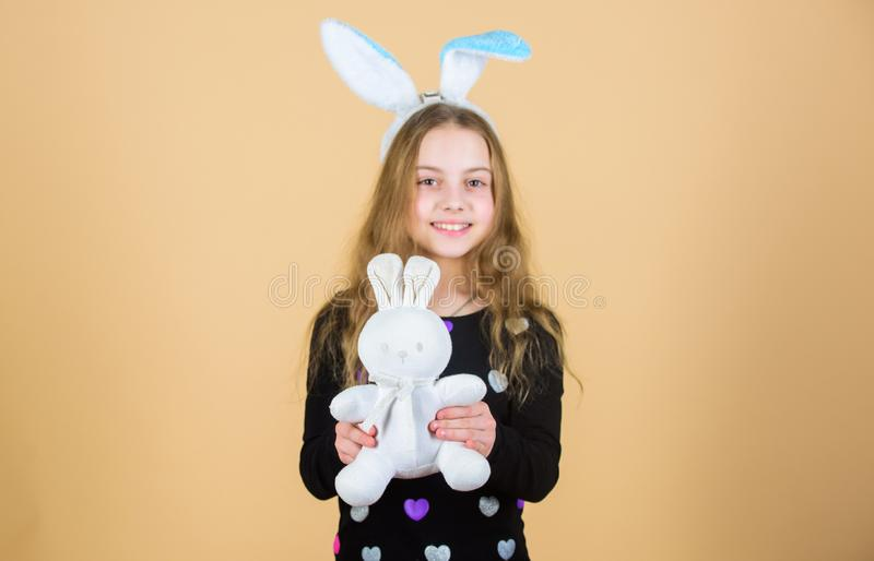 Hare is a symbol of fertility and spring. Small kid getting white hare gift on Easter day. Little girl holding Easter royalty free stock image