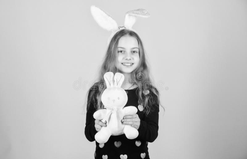 Hare is a symbol of fertility and spring. Small kid getting white hare gift on Easter day. Little girl holding Easter. Hare toy. Happy child playing with cute royalty free stock images
