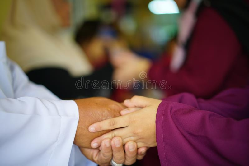 Hari Raya Aidilfitri concept. Hand of young women asking forgiveness during Eidul Fitri celebration royalty free stock image
