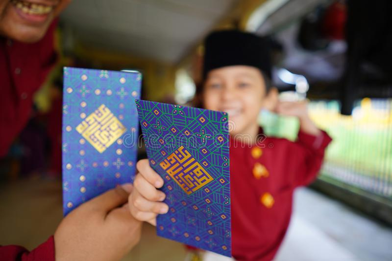 Hari Raya Aidilfitri concept. Rawang Selangor, Malaysia - June 16th,2018 : Little boys out of focus, showing their happiness reaction after received money pocket stock photo