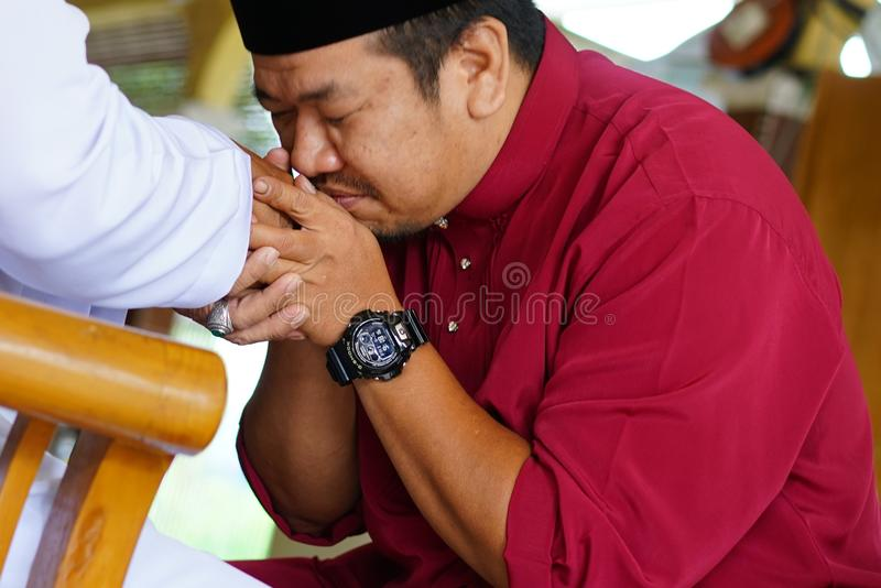 Hari Raya Aidilfitri concept. Rawang Selangor, Malaysia - June 16th,2018 : Son and father asking forgiveness during Eidul Fitri celebration stock images