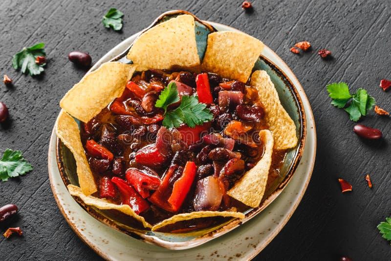 Haricot rouge avec des nachos ou des frites de pain pita, poivre et des verts de plat au-dessus de fond foncé Casse-croûte mexica photos stock