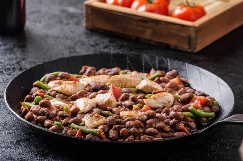 Haricots avec des tomates et poulet images libres de droits