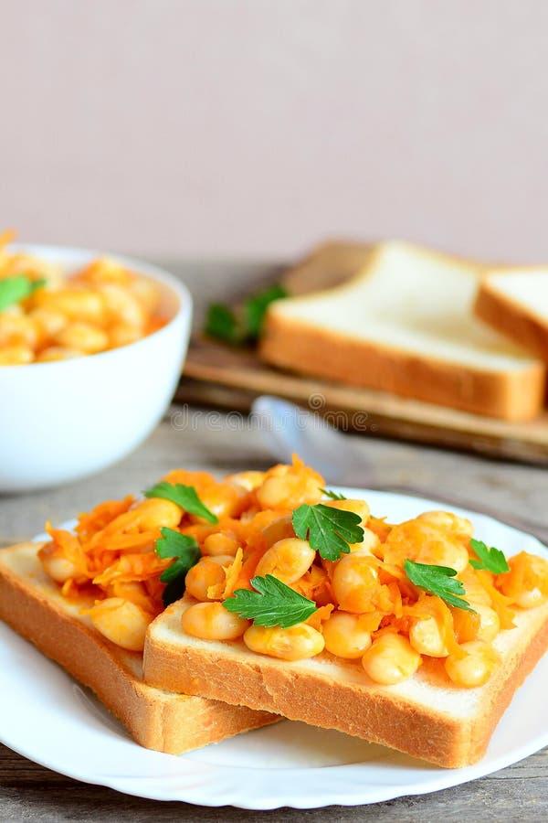 Haricots blancs cuits au four avec la carotte et le persil sur des tranches de pain blanc images stock
