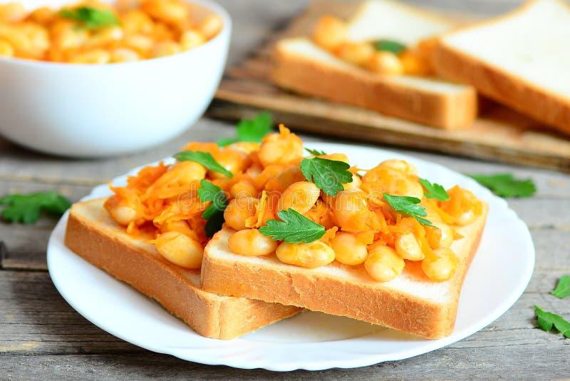 Haricots blancs cuits au four sur des haricots de pain grillé cuits au four avec la sauce de carottes, d'ail et tomate et garnis  photos libres de droits