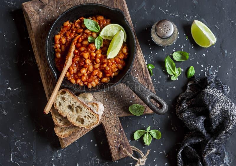 Haricots braisés en sauce tomate dans une casserole de fonte et un pain fait maison photo stock